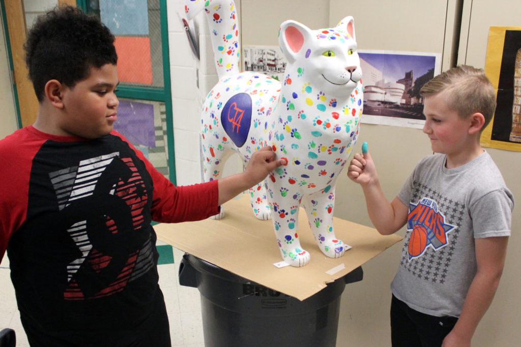 students stamp thumbprints onto cat statue