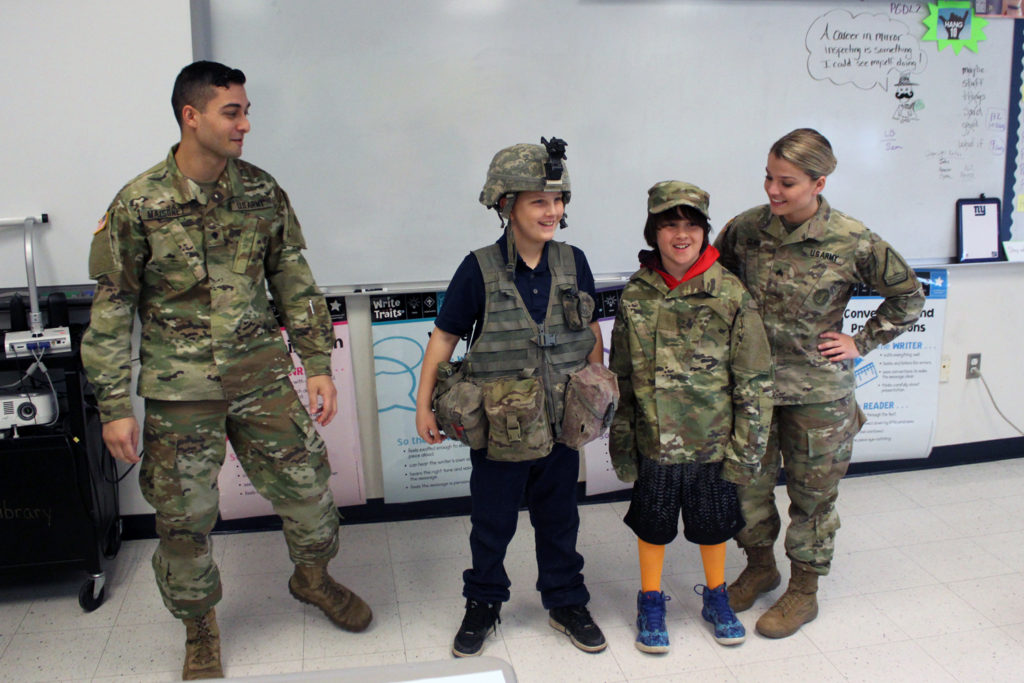 students try on army gear with National Guard Soldiers