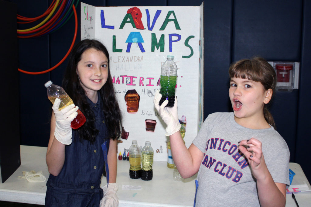 students hold up lava lamps they made