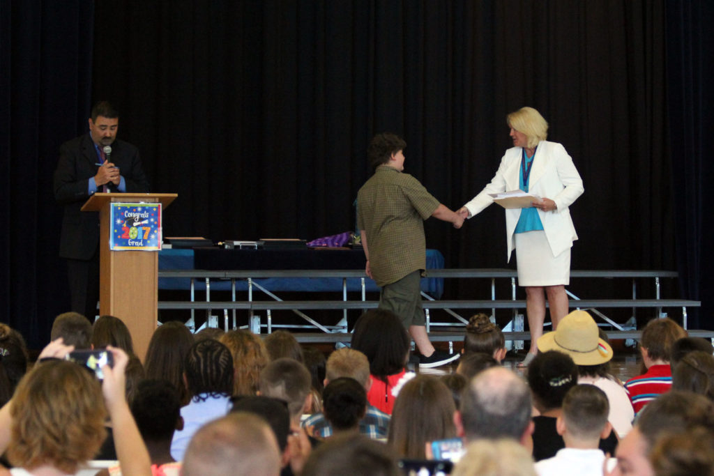 student walks across stage to shake hands with Mrs. Schlenker