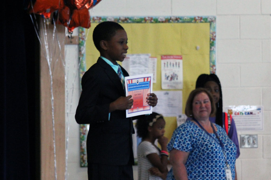 boy with moving up certificate