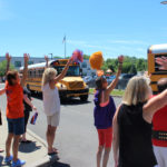 teachers wave goodbuy to students on buses