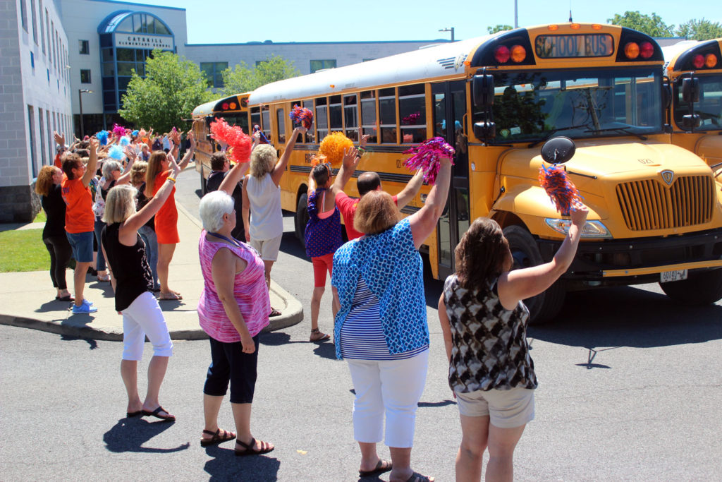teachers wave goodbye as busses roll out of elementary school parking lot