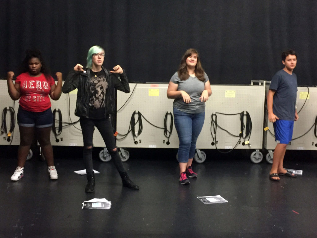 four student rehearsing for summer music camp's musical