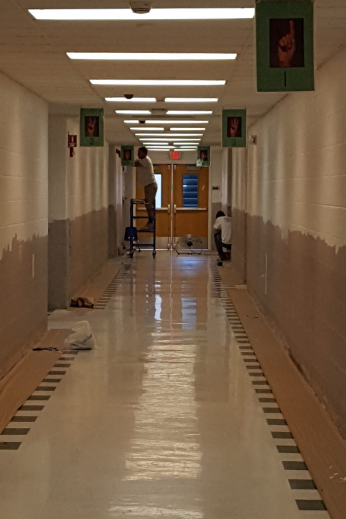 two painters painting beige hallway