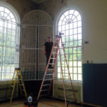 Window grates being reinstalled in the Middle School Gym