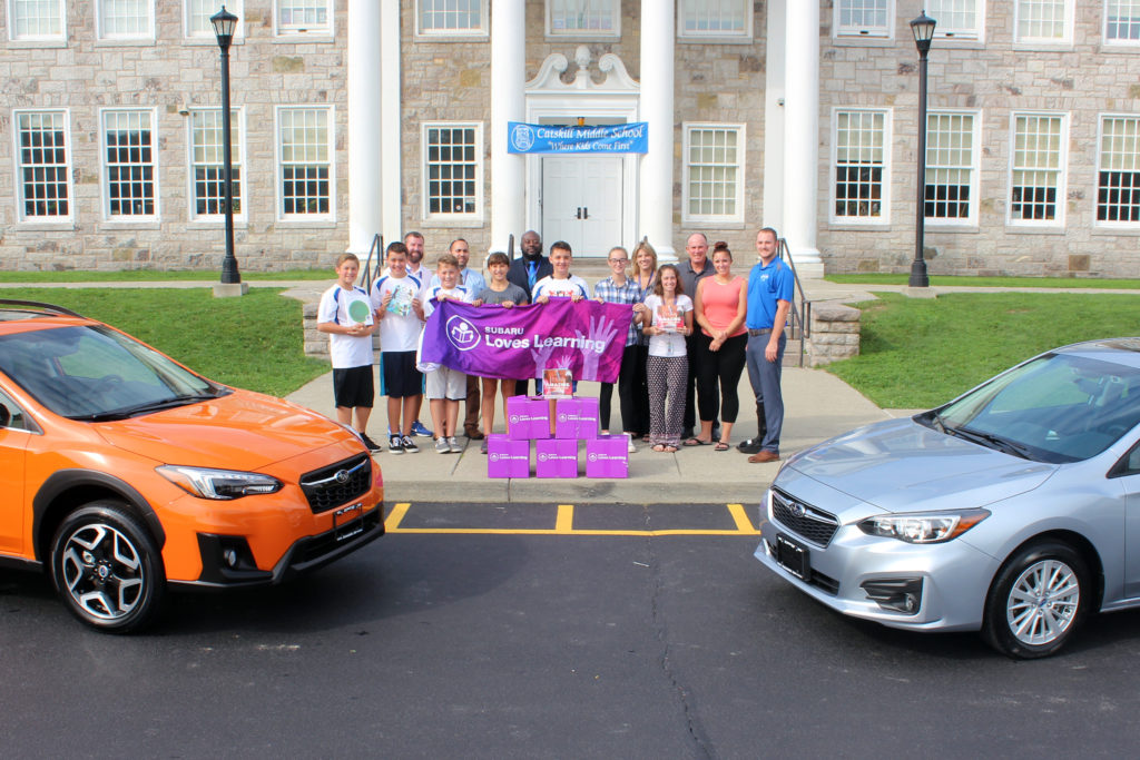 Group Photo of CMS and Lacy Subaru representatives with the books outside CMS