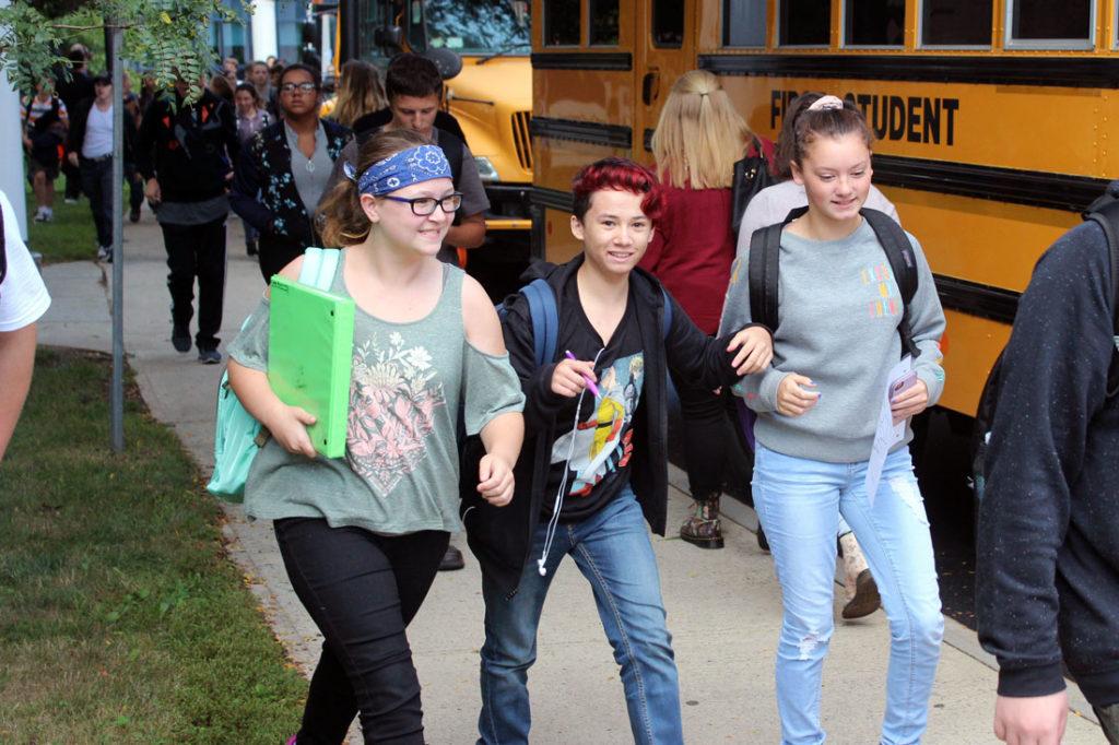 three high school students walking to bus