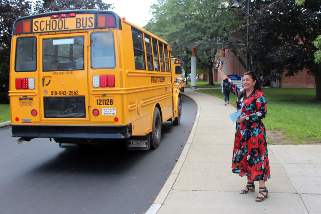 High School pricipal wave to busses
