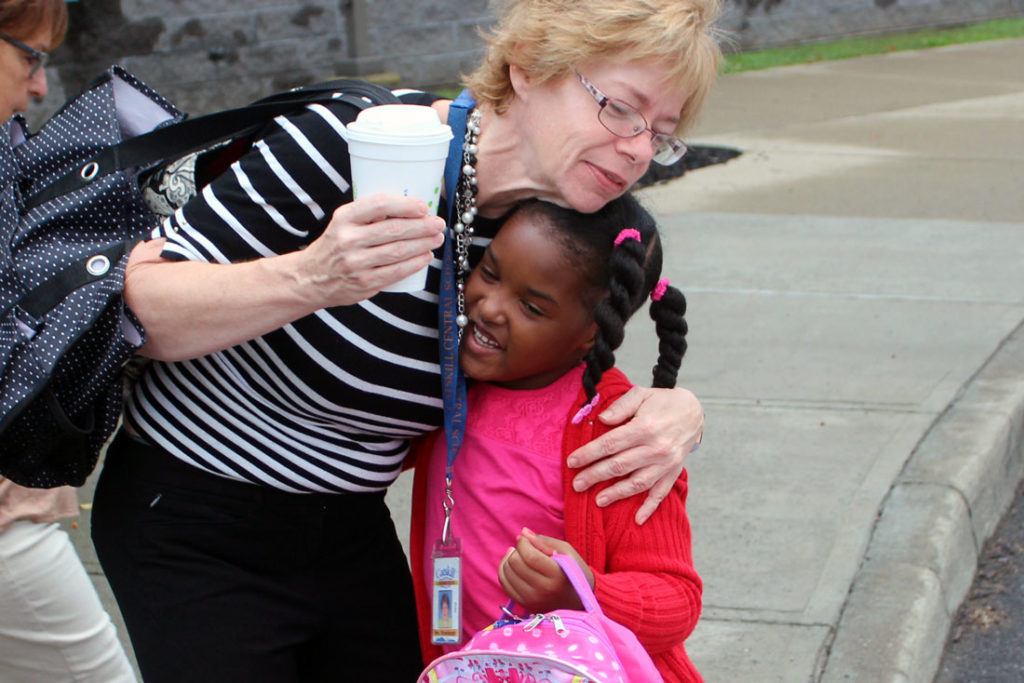 student give teacher aid a big hug