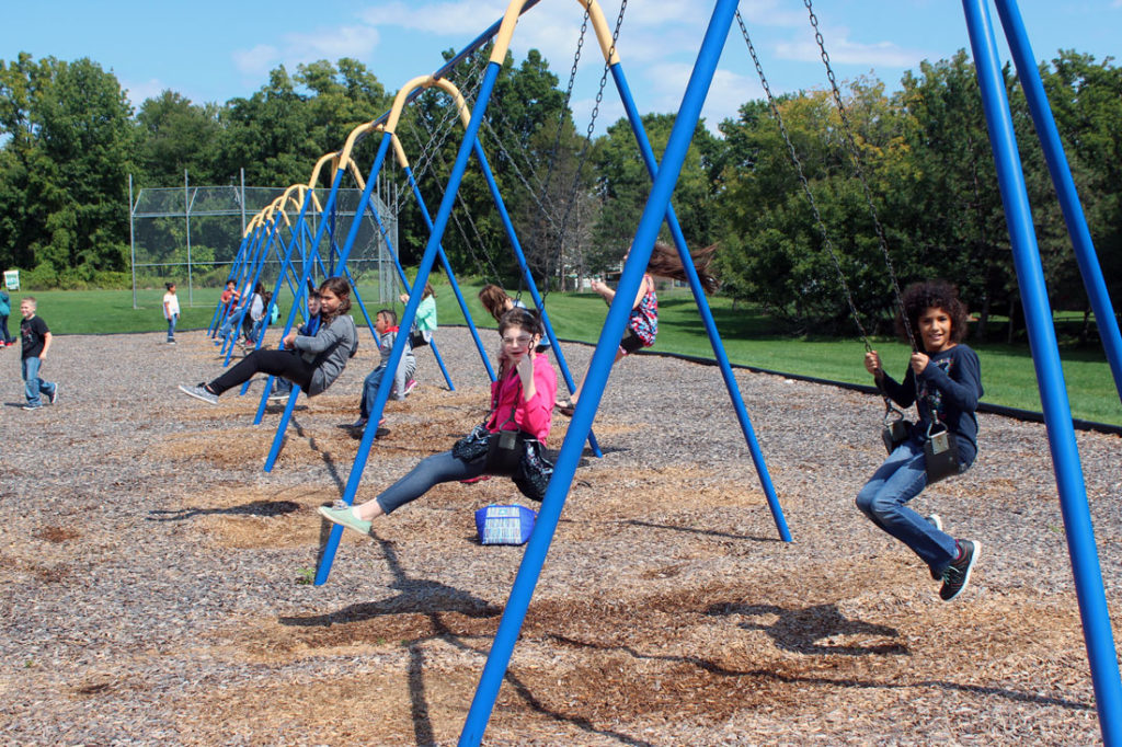 elementary students on the swings