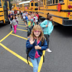 girl waves after getting off the bus