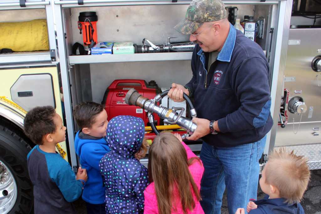 Firefighter shows students hose nozzle