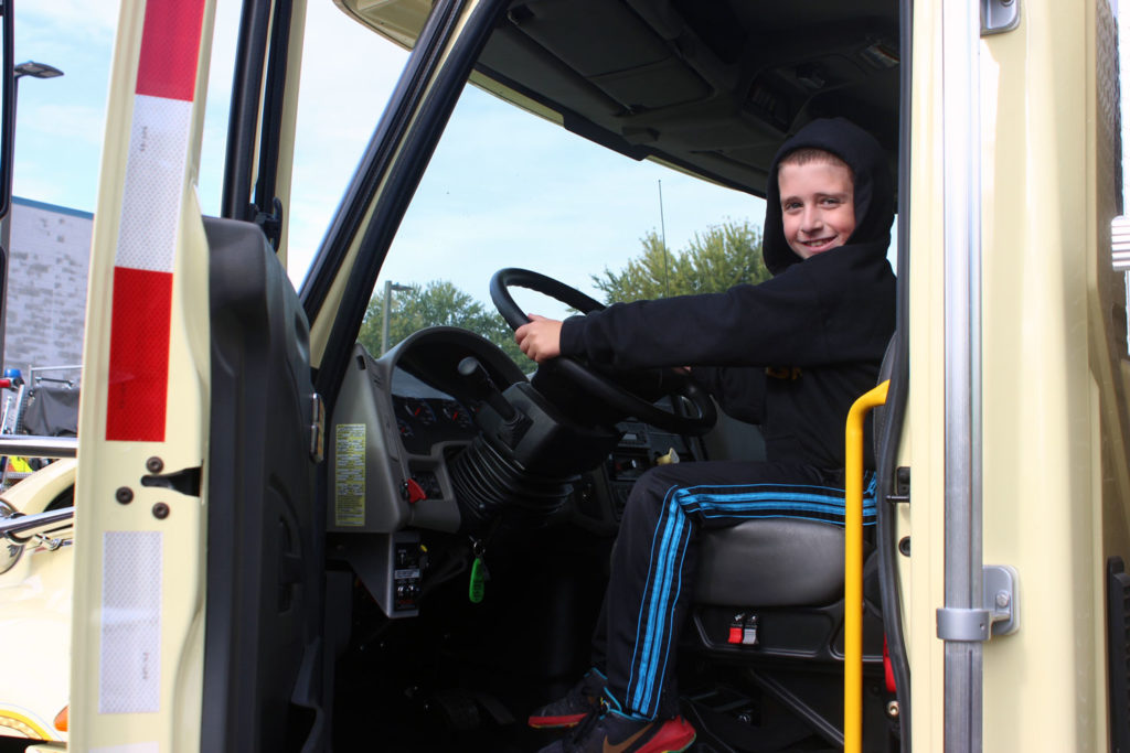 Boy behind the wheel of a fire tuck