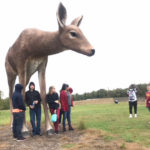students pose with deer sculpture