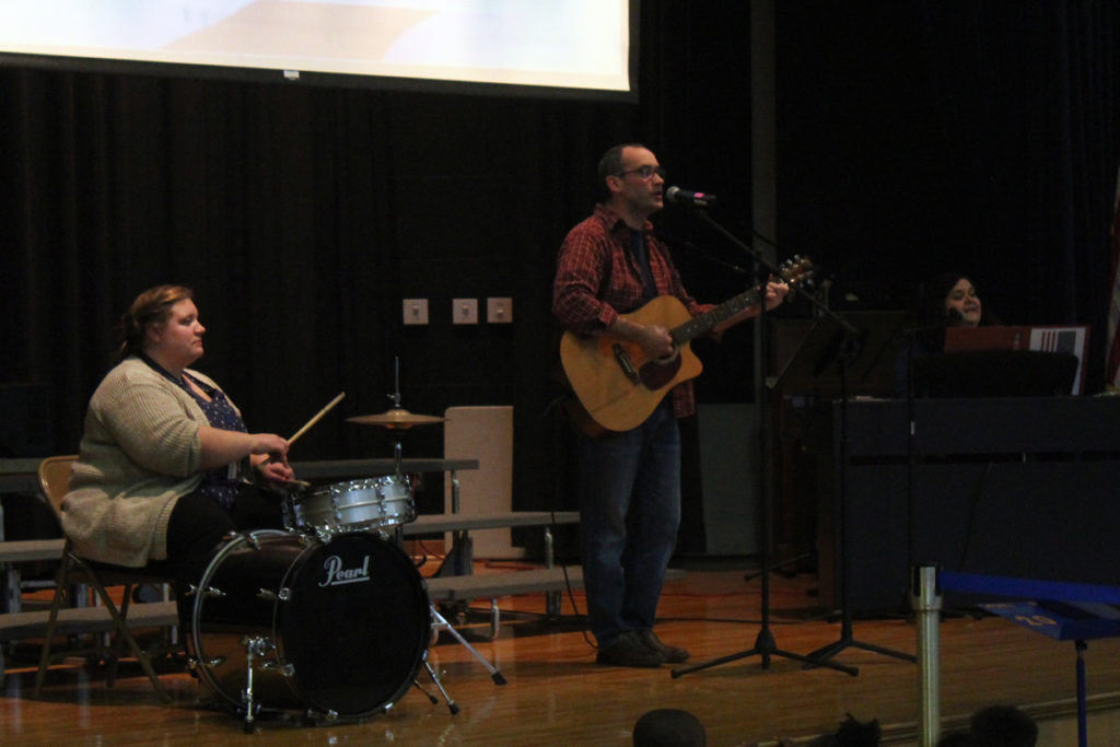 Mr. Thibault on guitar, Mrs. Verdichizzy on piano, and Mrs. Drewello on the drum kit,