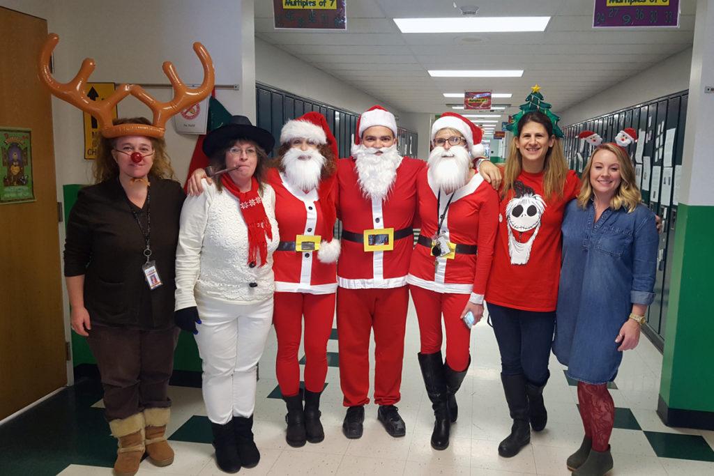 teachers dressed up like reindeer, snowman, santa, and elfs