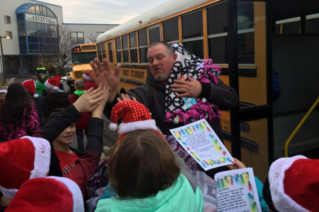 bus driver high-fives students