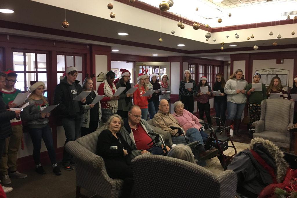students caroling in senior living center