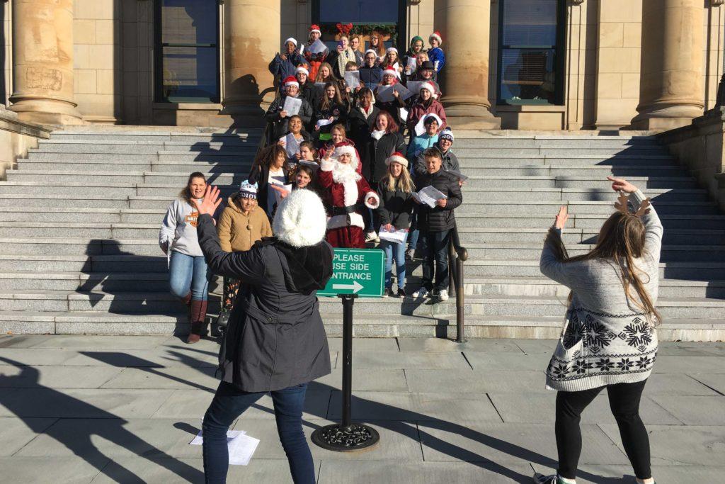 students caroling on courthouse steps