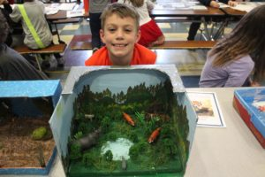 student poses with his diorama of faxes