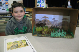 boy poses with diorama