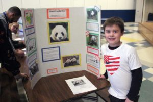 boy poses with display board on pandas