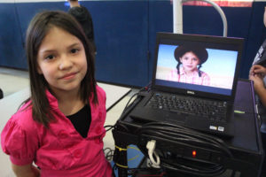 girl poses wit her video on computer