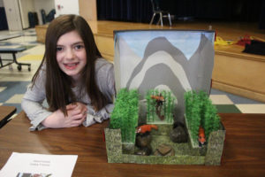girl poses with her diorama showing red pandas