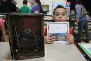 boy poses with book and diorama