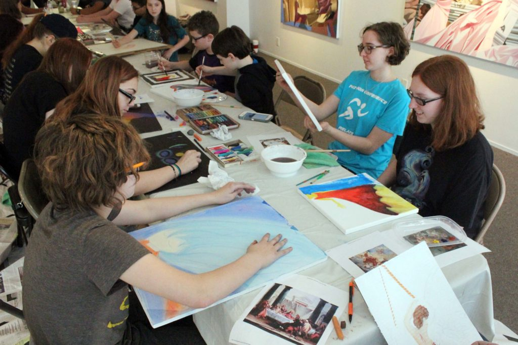 students creating artwork at table in middle of gallery