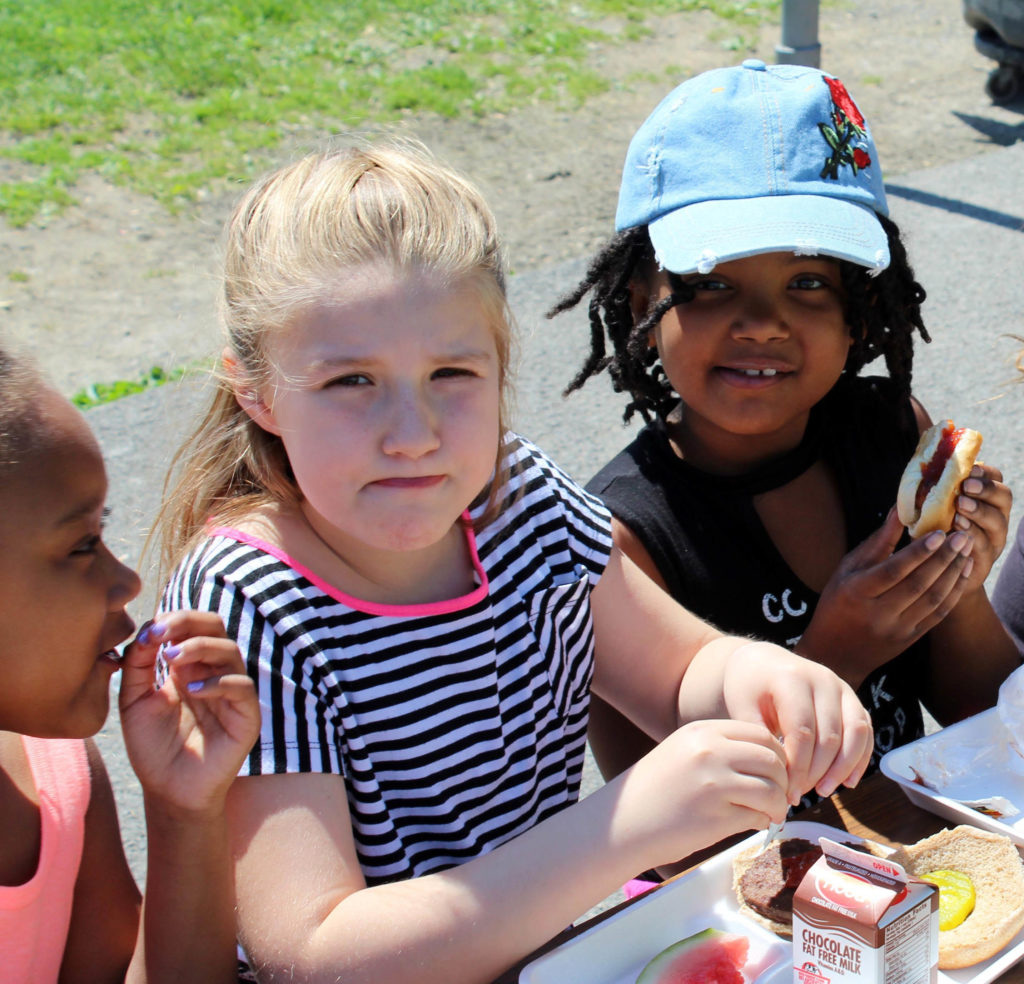 three girls eating lunch in the sun