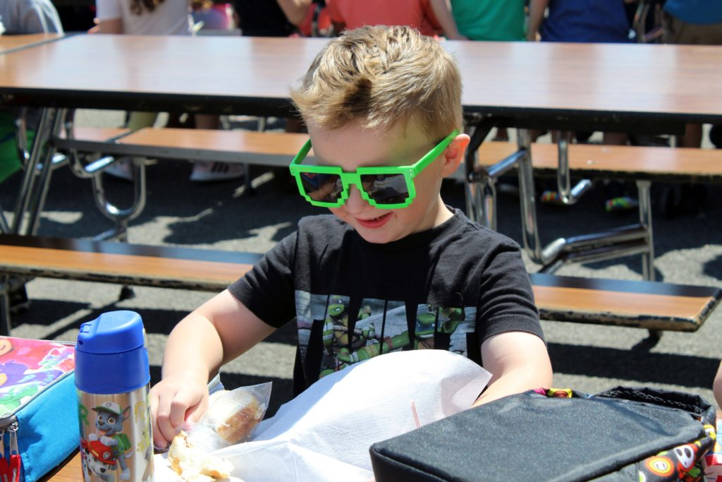 boy wearing shades eating lunch