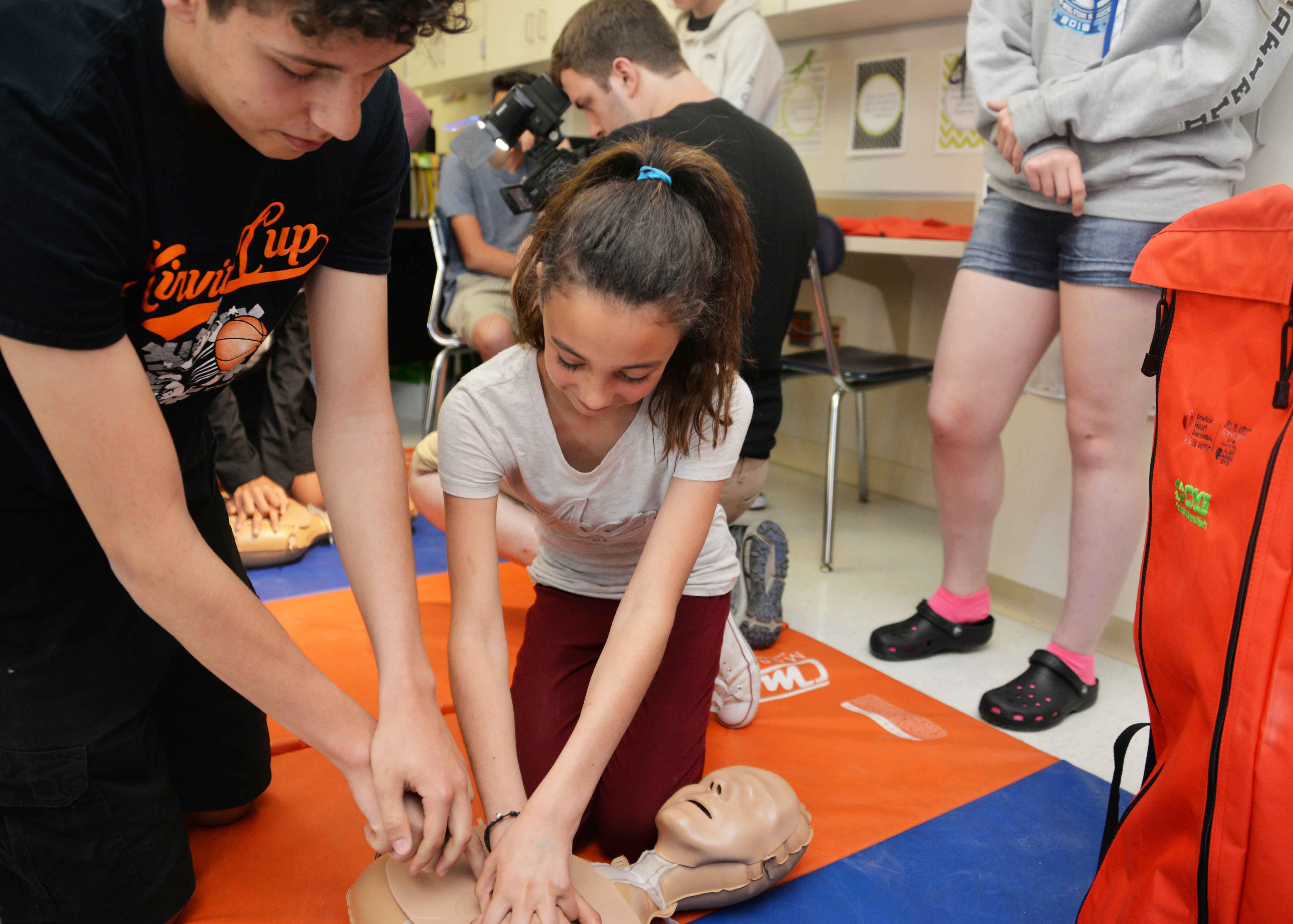Student shows younger student CPR