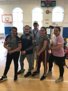 students pose with golf instructor