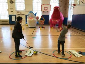 students take golf shots at giant cartoon character targets