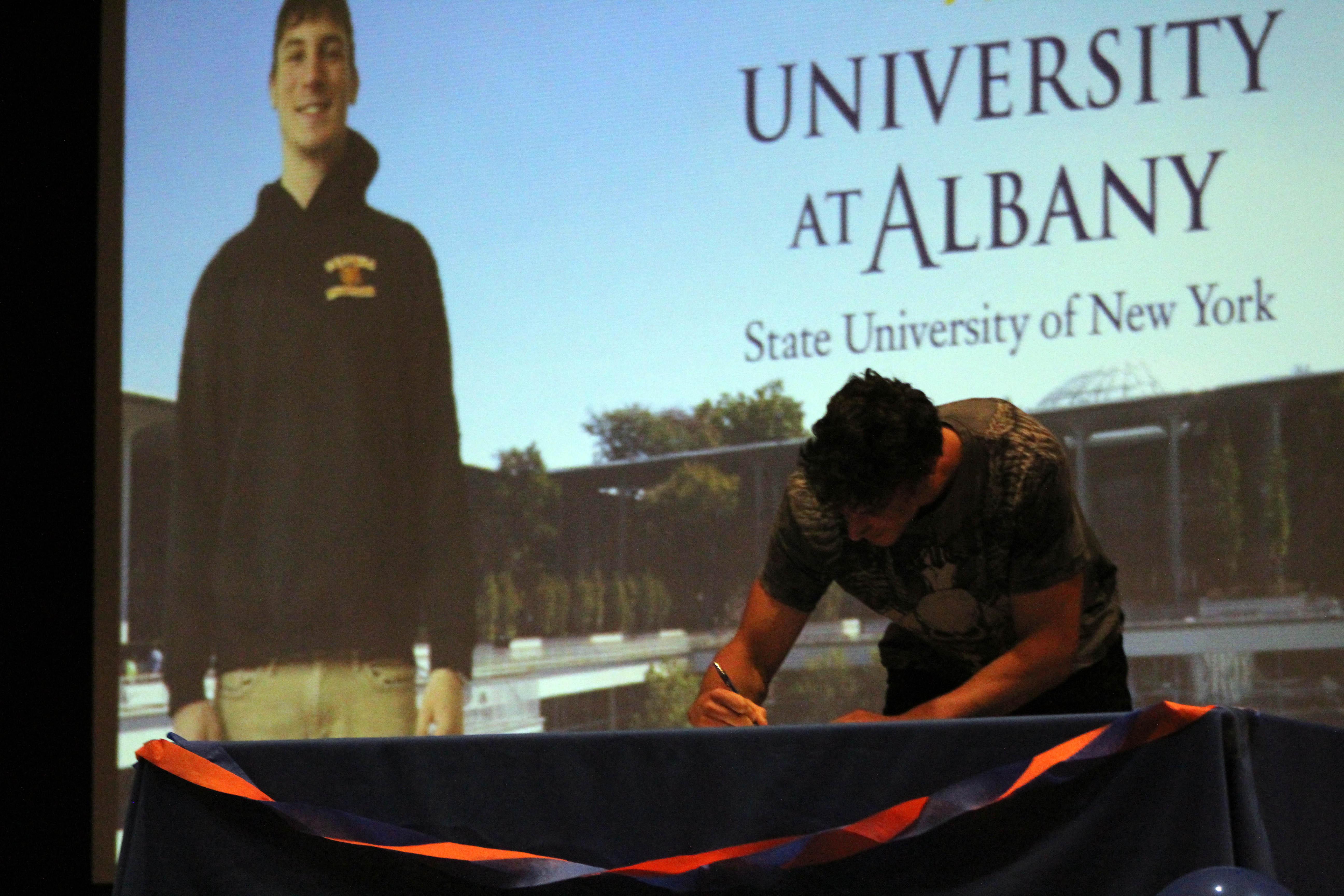 boy signs on senior signing day