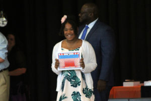 girl smiles as sheholds up certificate
