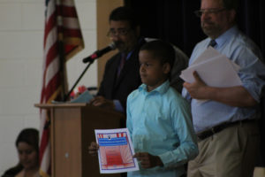 boy holds moving up certificate