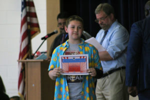 boy holds up moving up certificate