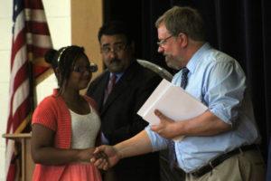 girl shakes hands with teacher