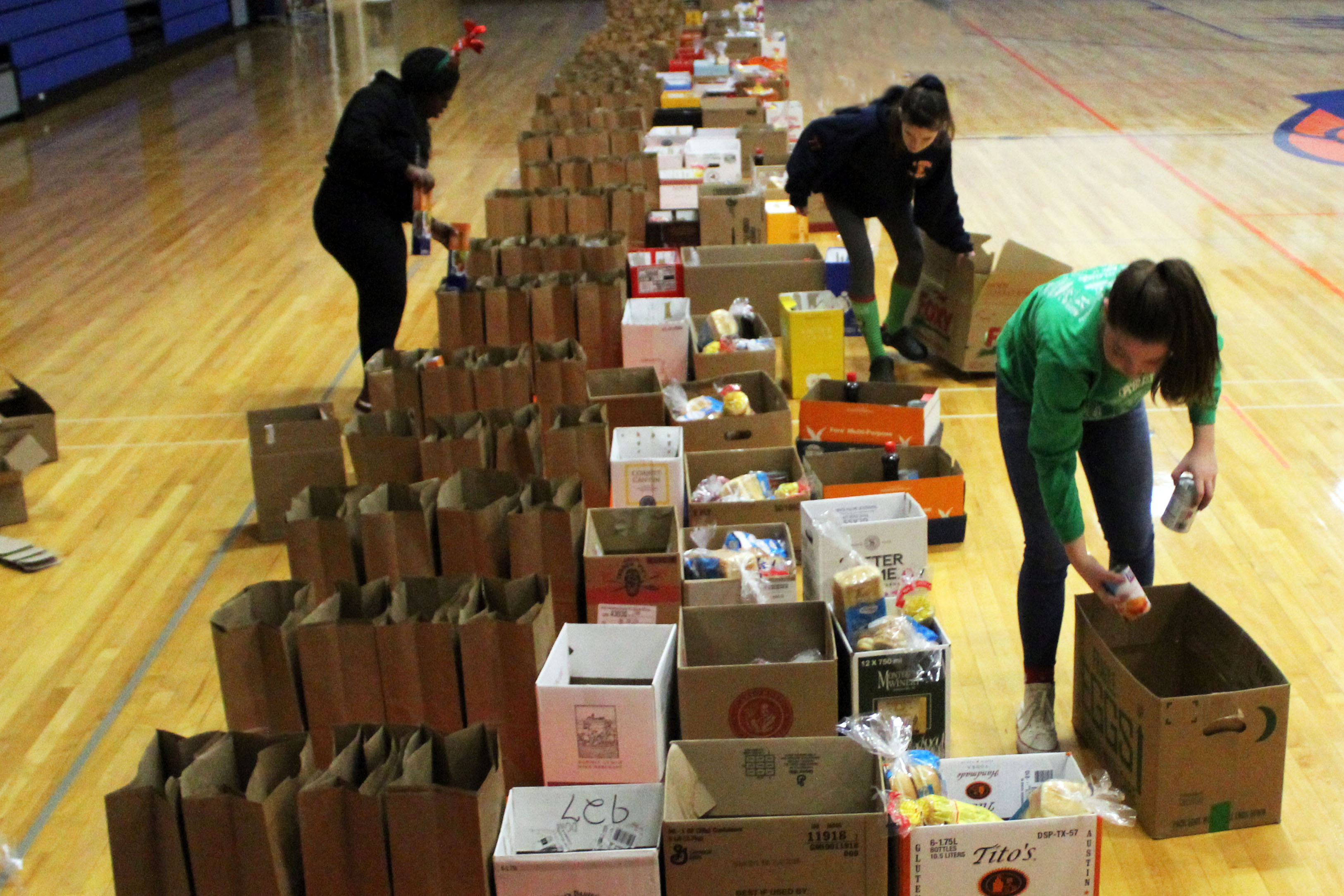 three girls pack long line of bgs with food on gym floor