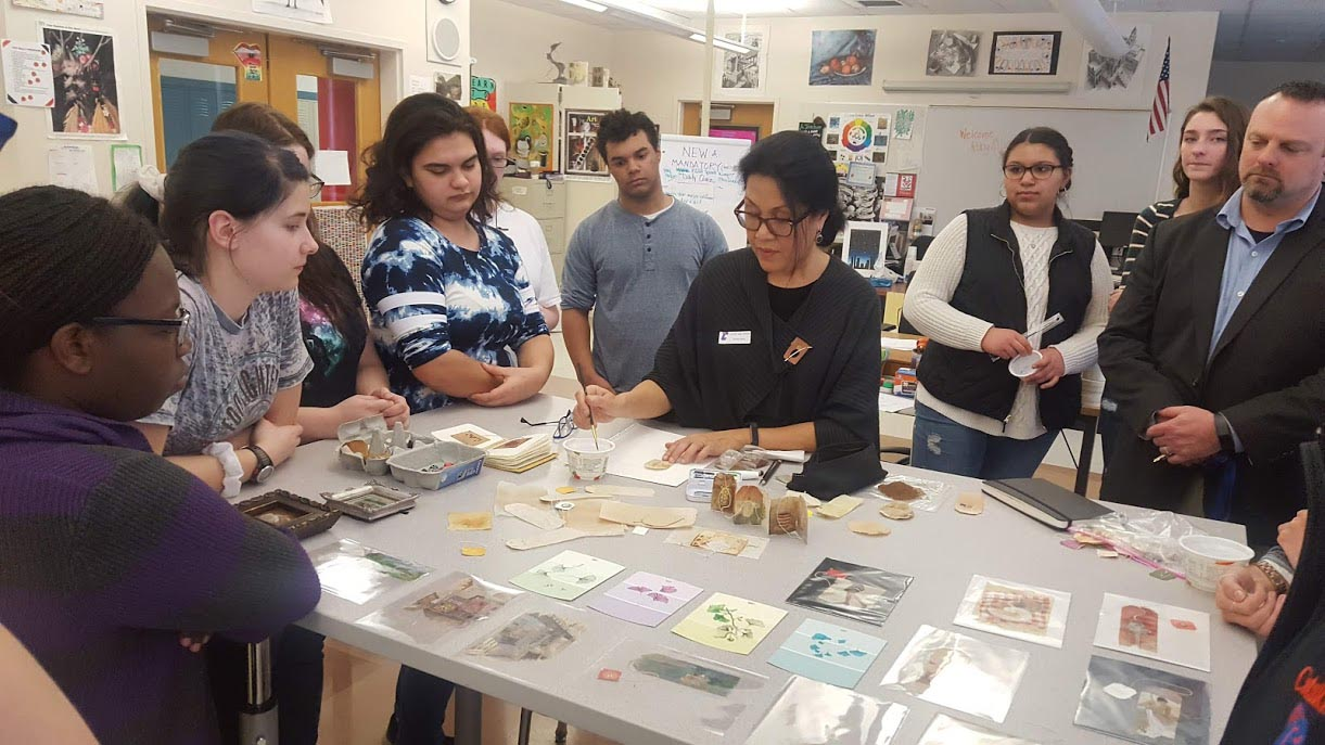 Ruby Silvious shows students her artwork at table