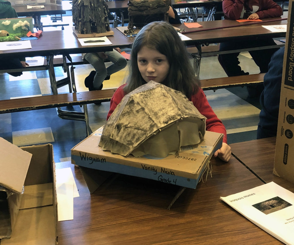 girl with model Native American dwelling