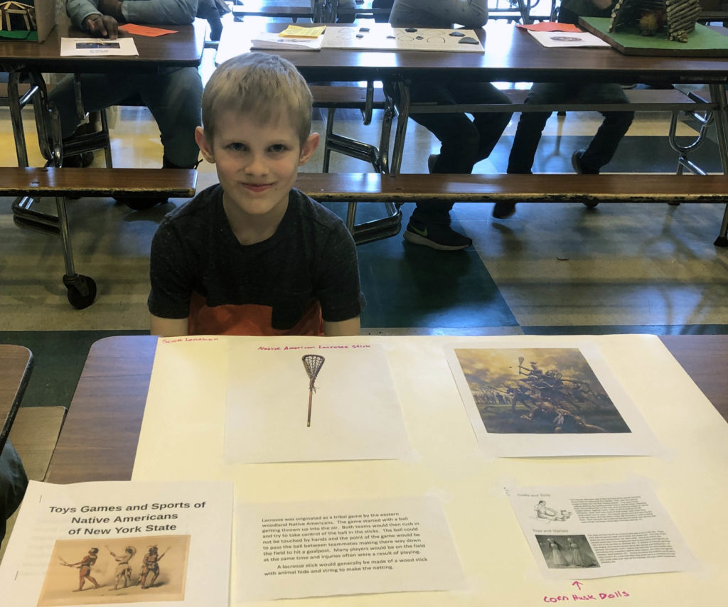 boy sitting at table with Native American display