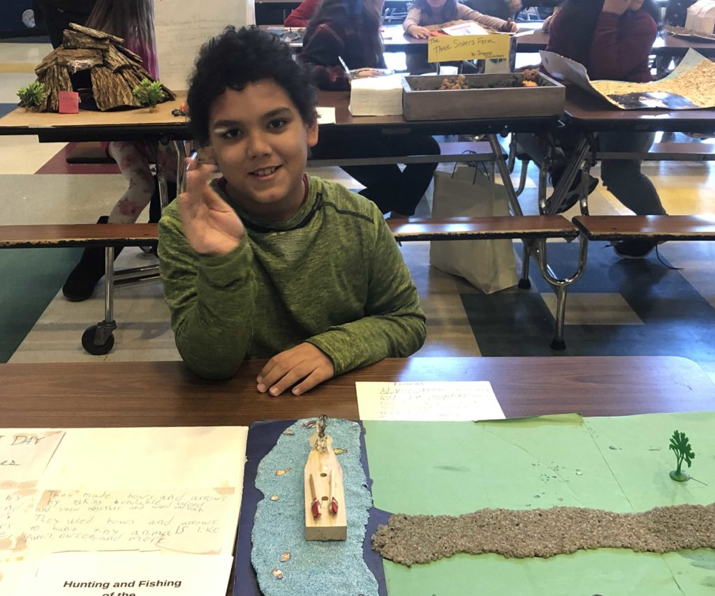 boy sitting at table with Native American diorama of river and fishing