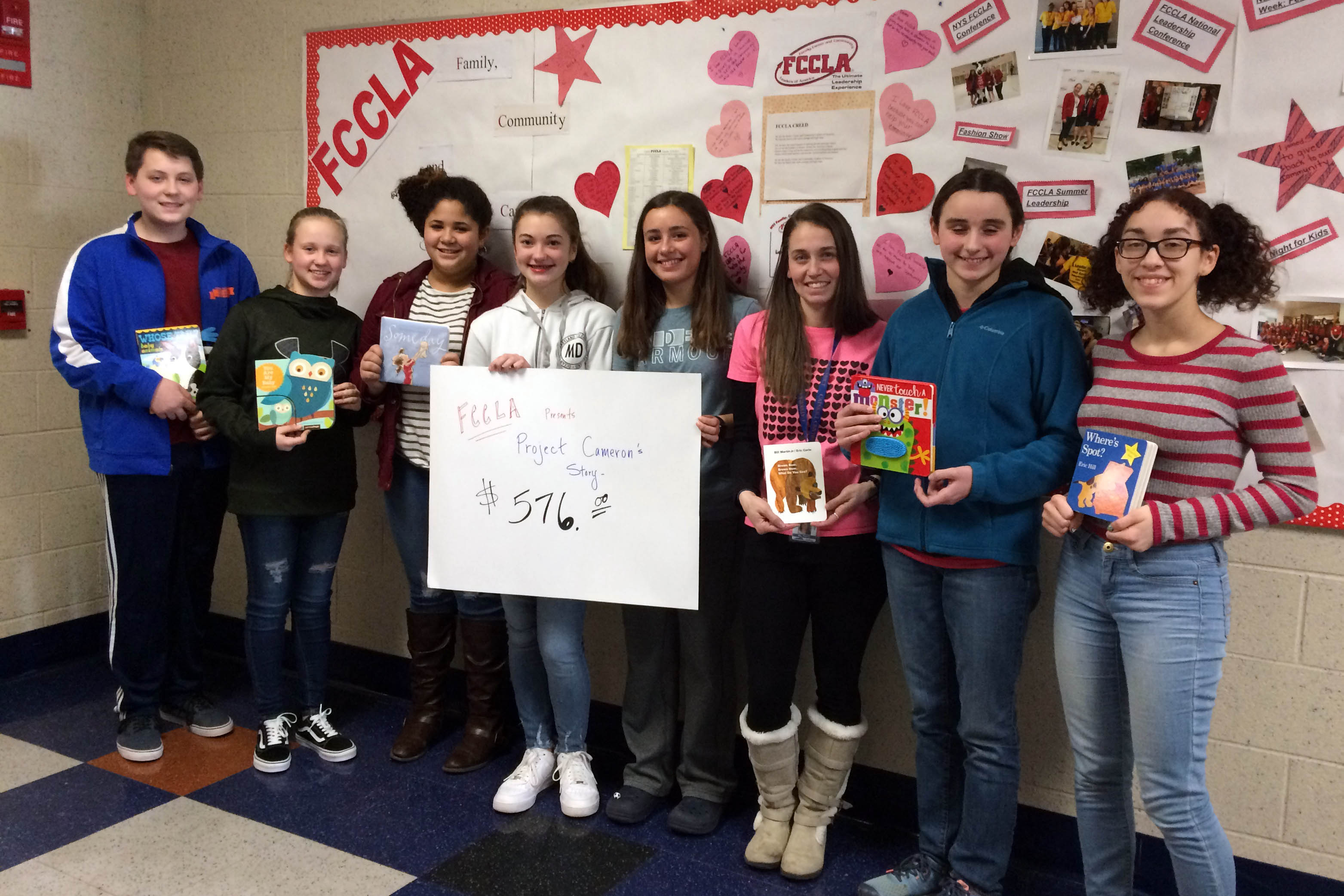 FCCLA representatives Christopher Konsul, Kaelyn Bulich, Alivia Westbrooke, Madison Hallam, Lauren Liberti, Mrs. Funk, Angelina Shanley, and Ariana Nieves pose with some of the books they collected and a sign that says FCCLA presents Project Cameron's Story $576