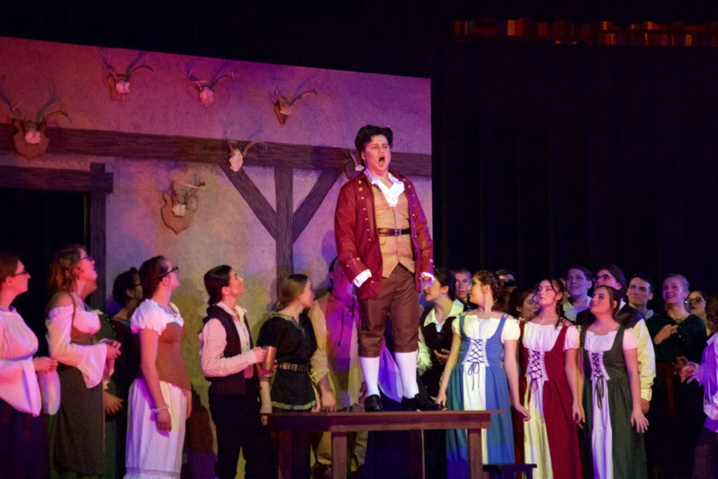 gaston sings on a table while tavern people look up to him