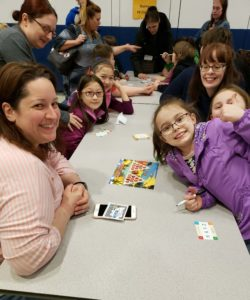 mothers and daughters palying math games at table