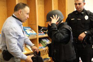 police officer helps boy try on SWAT helmet
